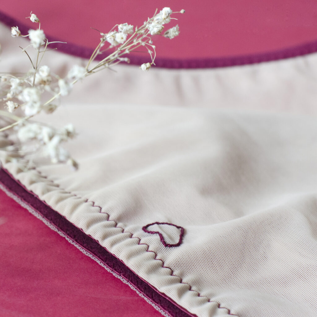 détail échancrure du dos d'une culotte nouée biais bordeaux sur tulle stretch couleur rose poudré
