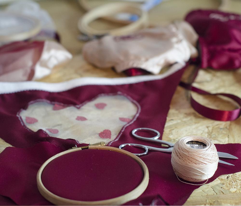 culotte bordeaux à plat avec un tambour à broderie des ciseaux et du fil